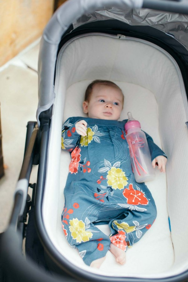 Summer Brennan wearing Tea Collection in an Uppa Baby Vista Stroller with a Dr. Browns Bottle