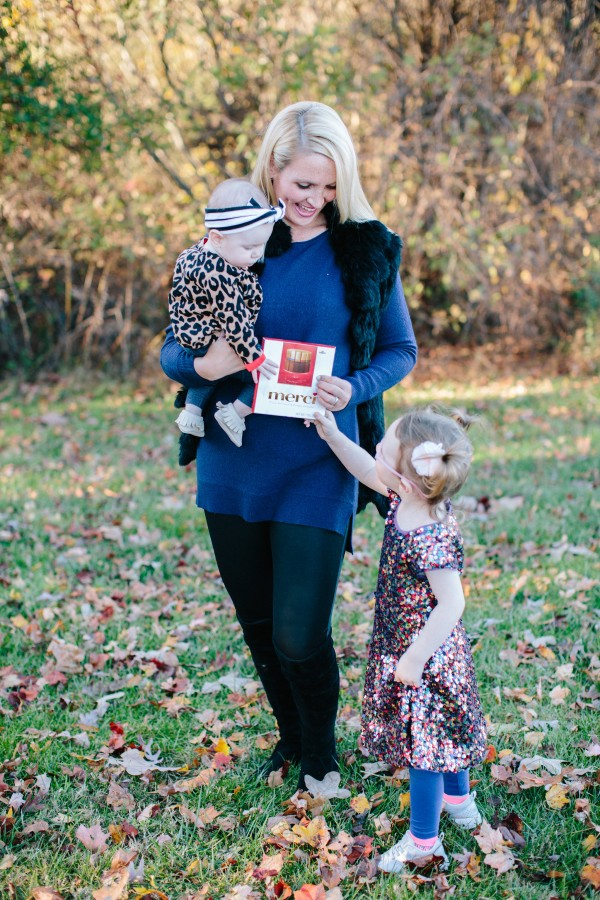 Blogger Kate Brennan of Dress Your Guests wearing a fur vest and halogen navy sweater with her daughters holding merci chocolate