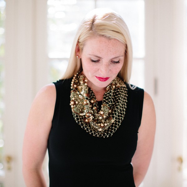 Blogger Kate Brennan wear a black top with an intricate statement necklace, bold lip, necklace, baubles, gold