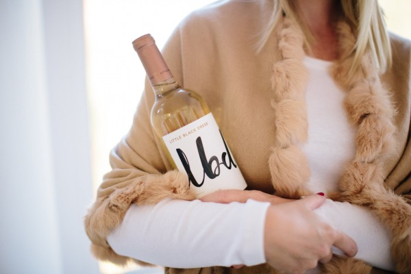 Blogger Kate Brennan sips on LBD white wine during happy hour while wearing a J. McLaughlin wrap and hat, vino, happy hour, J. McLaughlin, sip, mom style, mommy blogger, DYG, Dress Your Guests