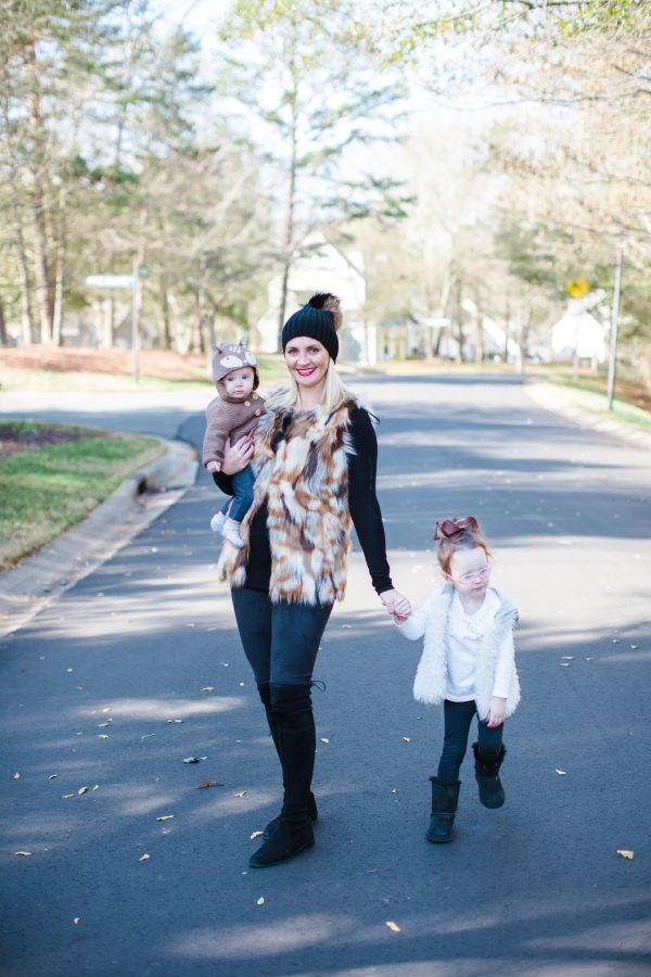 Blogger Kate Brennan wears a faux fur vest, spanx leggings and spanx leggings stands in the street holding her daughter Summer while holding her daughter Isabella's hand