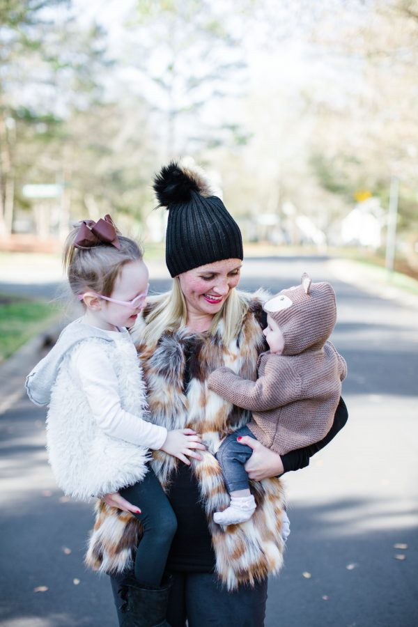 Blogger Kate Brennan wears a fur vest and pom-pom beanie and holds her daughters Summer and Isabella in her arms