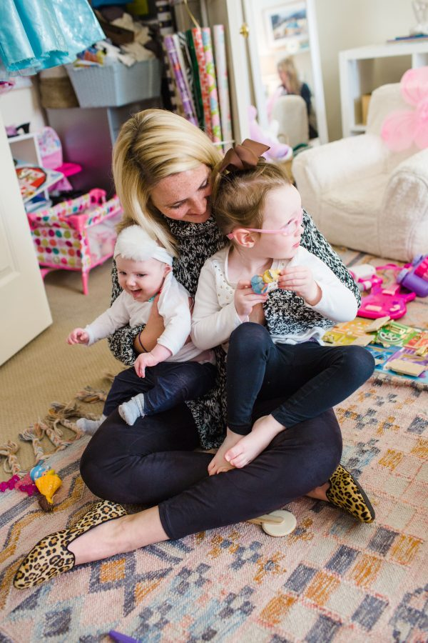 Kate Brennan wearing a Tunic Sweater, Spanx Leggings and Birdies Slippers while holding her two daughters
